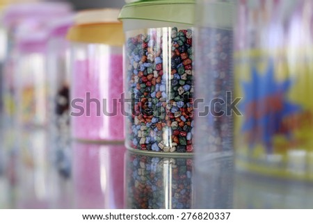 Many colorful little sweets yellow pink red blue green orange white brown colors in plastic jars, horizontal picture - stock photo