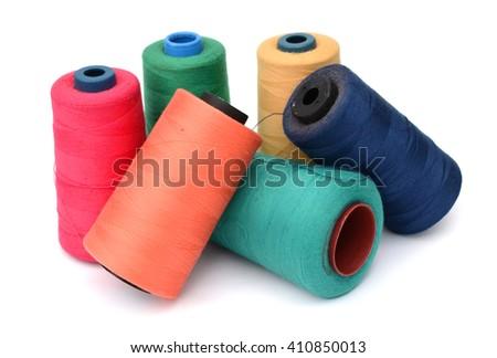 Many-coloured bobbins of thread isolated on white - stock photo