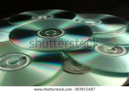 Many compact disks CD on pile against black background. - stock photo
