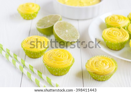 Many cupcakes with yellow cheese cream, lime and drinking straws on white background. Selective focus - stock photo