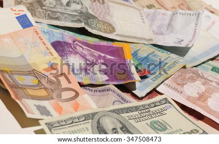 Many different bank notes - side view - different currencies as colorful background concept global money. Selective focus - stock photo