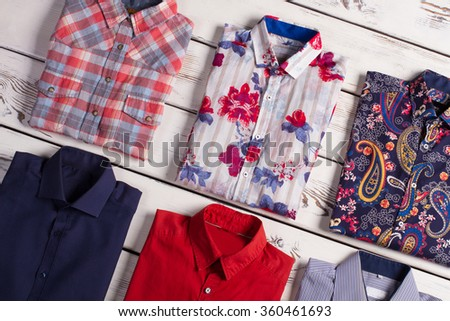 Many different bright stylish men's shirts with different colors and prints on old wooden background. - stock photo
