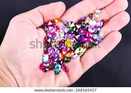 Many different natural gemstones in hand - stock photo
