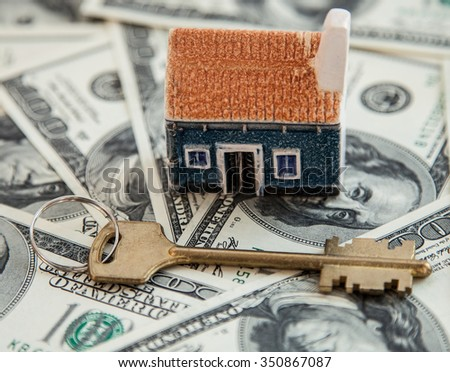 Many dollar banknotes, key and a house model; concept of buying a house - stock photo