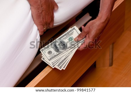 many dollar bills are hidden under the bed - stock photo