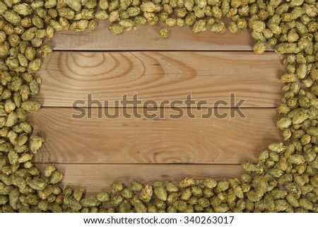 many dried hops on old weathered wooden board - stock photo