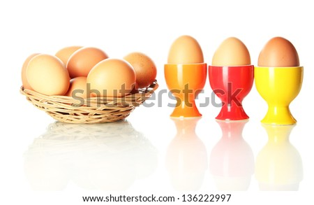 Many eggs in basket and in egg cup isolated on white - stock photo