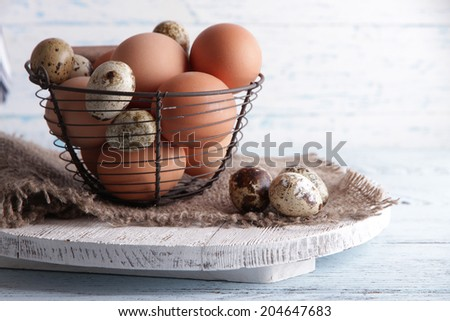 Many eggs in basket on wooden background - stock photo