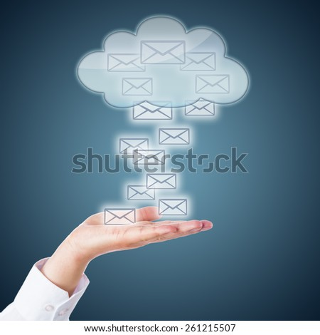 Many email icons landing in an open palm. Or rising up from the hand into a receptive cloud computing symbol. Business metaphor for online correspondence and mobile computing. Steel blue background.  - stock photo