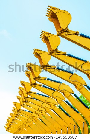 many excavator buckets ready to do the job. Let's dig - stock photo