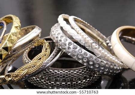 Many fashion bracelets on black background - stock photo