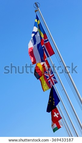 many flags of many nations world waving in the blue sky - stock photo