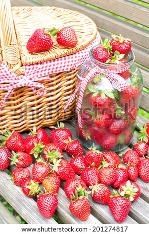 Many fresh ripe strawberry in basket and glass jar on wooden background. Bounty summer crop in garden. Outdoors. - stock photo