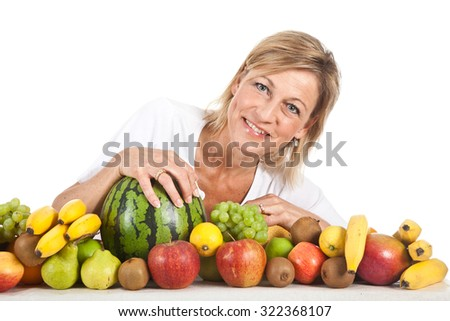 Many fruits stacked together and cute woman - stock photo