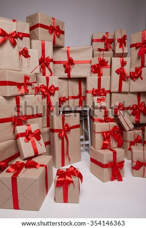 Many gifts, boxes with gifts covered with red satin and silk ribbon with big bow, merry Christmas and a happy new year, surprise, wishes, birthday or holiday  - stock photo