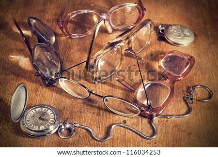 many Glasses and watch lying on a wooden table - stock photo