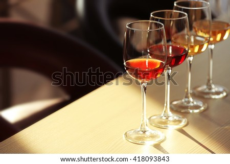 Many glasses of different wine in a row on a table - stock photo
