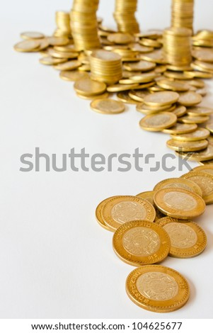 many golden coins making curved path on white background, mexican ten pesos coins - stock photo