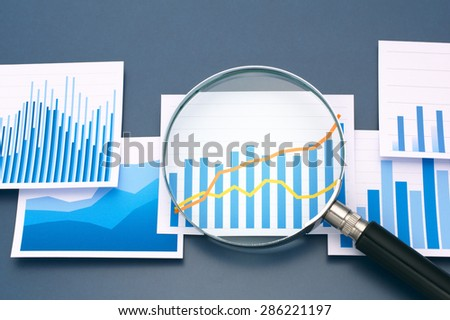 Many graphs and magnifying glass on dark blue background. Analyzing data with magnifying glass.  - stock photo