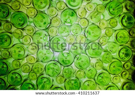 Many green beer bottle bottom under bright light background. - stock photo