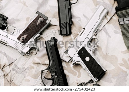 Many Guns on Military texture. Handguns on camouflage background. 9mm, 11mm Pistols. (Process With TV Scan line effect) - stock photo
