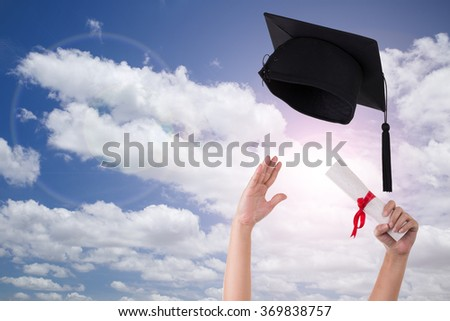 Many hand holding graduation hats on background of blue sky - stock photo