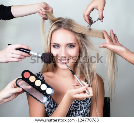 many hands applying make up on a woman head - stock photo