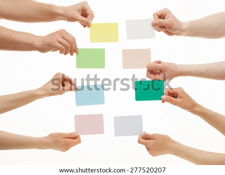 Many hands holding colorful paper cards on white background - stock photo