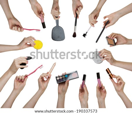 many hands holding different make up equipment cut out on white background  - stock photo