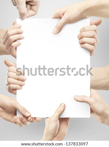 many hands holding poster on gray background - stock photo