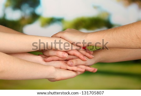 Many hands on nature background - stock photo