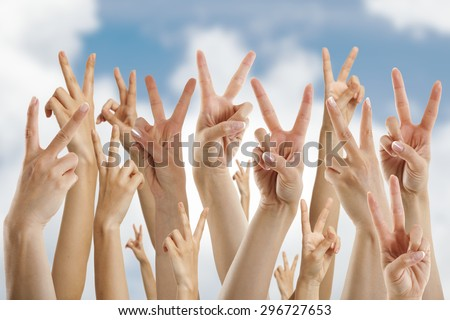 many hands showing victory sign, isolated on blue sky and clouds - stock photo