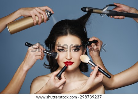 Many hands with cosmetics brush, shadows doing make up of glamour asian girl  - stock photo