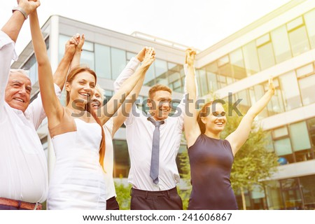 Many happy business people holding their arms up and cheering - stock photo