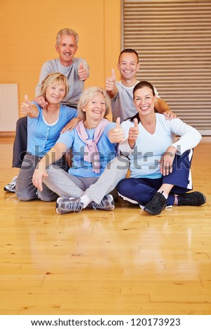 Many happy seniors holding their thumbs up in a sports club - stock photo