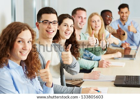 Many happy students holding their thumbs up in class - stock photo