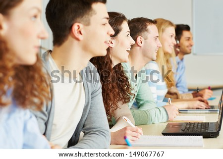 Many happy students learning together in the classroom of a school - stock photo