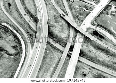 Many highways crossing over each other with cars and trucks driving on them. - stock photo