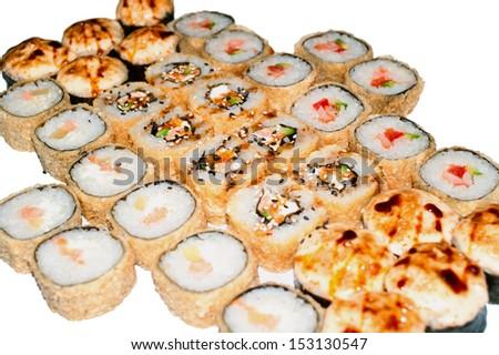 many hot sushi and sushi rolls on white background. Shallow DOF, isolation  - stock photo
