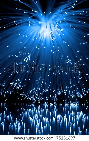 Many illuminated blue fiber optic light strands cascading down and reflecting into the foreground. Black background - stock photo