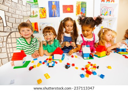 Many kids play with plastic blocks in classroom - stock photo