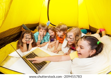 Many laughing with laptop children in a tent - stock photo