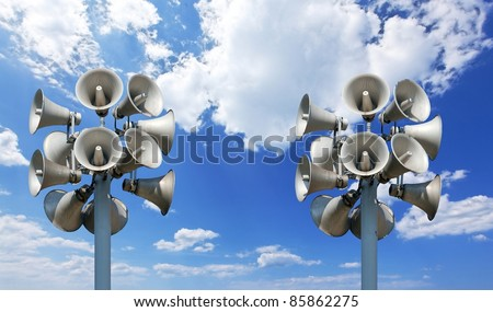 Many loudspeakers against cloudy sky - stock photo