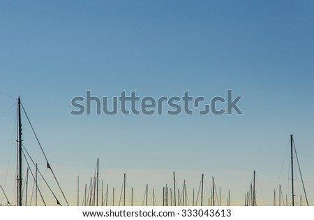 many modern ship masts rising into a beautiful and colorful clear sky - stock photo