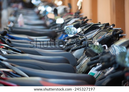 many motorcycles in a line at a downtown parking lot - stock photo