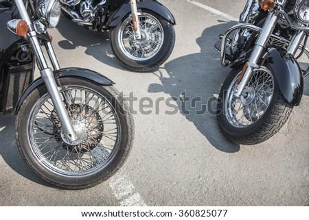 many motorcycles on parking on asphalt  close up - stock photo