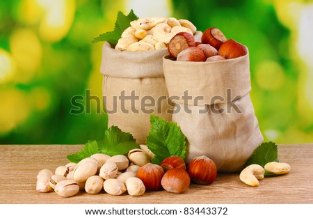 many nuts in bags on green background - stock photo