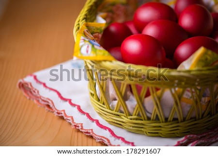 Many of Red Easter Eggs in a Yellow Basket on a Wooden Table - stock photo