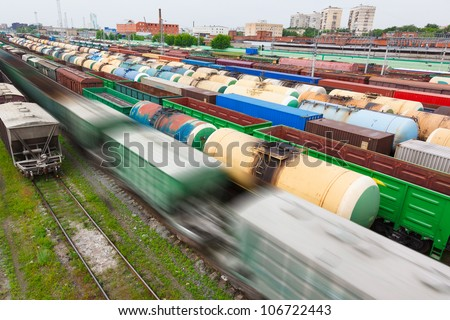 many oil tanks, containers and cars at the railroad station in bad weather - stock photo
