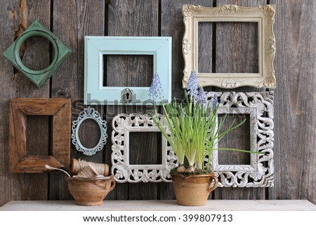 Many old frames of rectangular, square, oval, composition with vintage wooden frames, white, brown, gold, green, blue, fresh flower, spool, twine, clay cups - stock photo